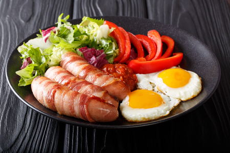 English breakfast: Pigs in blankets fried sausages wrapped in bacon, eggs, sauce and vegetable salad close-up on a plate on a table. horizontal
