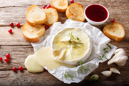 French melted Camembert with toast and cranberry sauce close-up on the table. Horizontal top view from above, rustic style