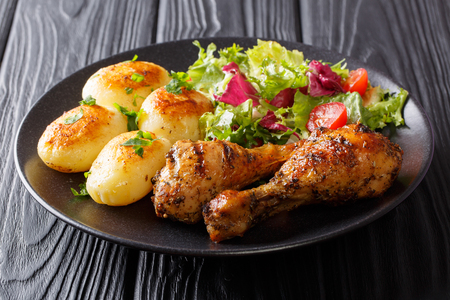 Hot grilled chicken legs with potatoes and fresh salad close-up on a plate. horizontal