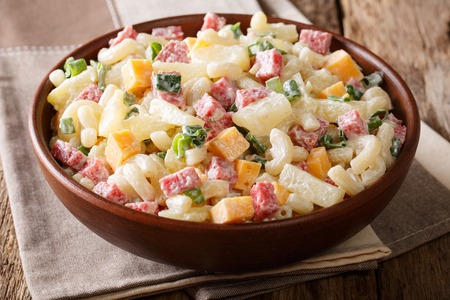 Hawaiian cuisine: salad with pasta, ham, pineapple, onion, cheddar cheese with mayonnaise close-up in a bowl on the table. horizontal, rustic style