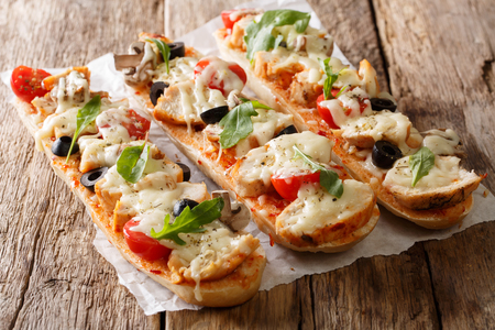 Hot tasty cut baguette baked with chicken, cheese, tomatoes, olives and mushrooms close-up on the table. horizontal