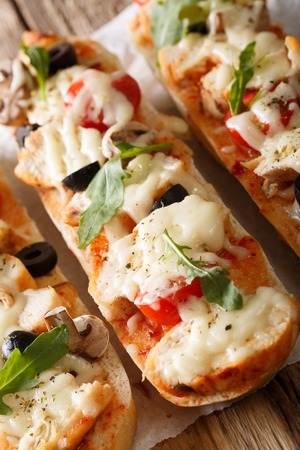 Hot sandwich casserole pizza with chicken, mozzarella cheese, tomatoes and mushrooms close-up on the table. vertical