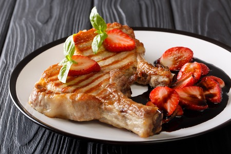 Pork grilled steak with basil and balsamic strawberry sauce close-up on a plate on a table. horizontal