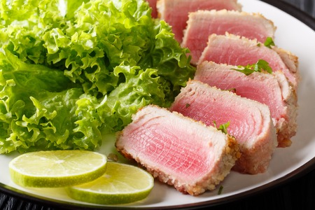 Tuna steak in breading Panko with lettuce and lime closeup on a plate. horizontal