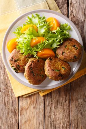 Los panqueques caseros de atún con especias se sirven con primer plano de ensalada de verduras frescas en un plato sobre la mesa. vista superior vertical desde arriba