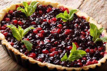 Summer dessert: tart with currant berries, blueberries and cranberries close-up in a baking dish on a table. horizontal