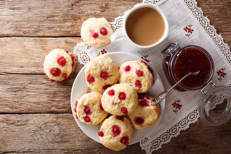 English buns sconces with red currants are served with English tea and jam close-up on the table. horizontal top view from above