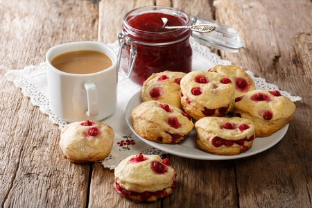 Freshly baked English scones with berry, tea with milk and jam close-up on the table. horizontal
