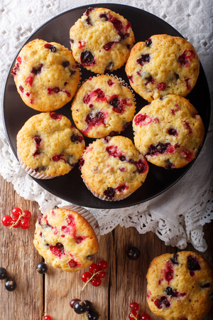 Freshly baked muffins with black and red currant berries close-up on the table. Vertical top view from above