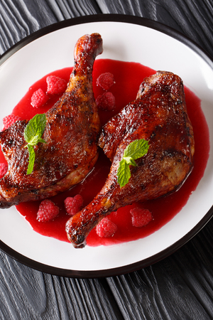 Fried duck leg with raspberry sauce decorated with mint closeup on a plate on the table. vertical Stock Photo
