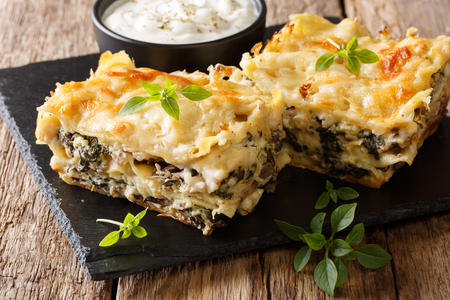 Casserole of lasagna with chicken breast, wild mushrooms, cheese, herbs and bechamel sauce close-up on a slate plate on a wooden table. horizontal Stock fotó