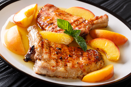 Summer food: grilled spicy pork with a bone with glazed peaches and mint closeup on a plate. horizontal