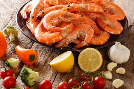 boiled tiger shrimps on a plate and fresh vegetables close-up on a table. horizontal