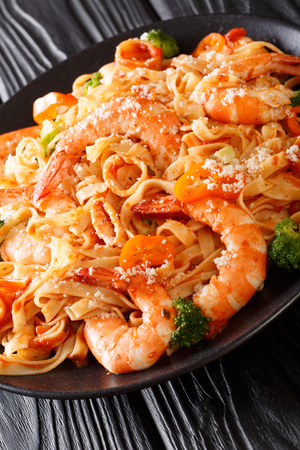 Recipe Italian pasta fettuccine with shrimp, squid, broccoli, cheese with tomato sauce closeup on a plate. vertical