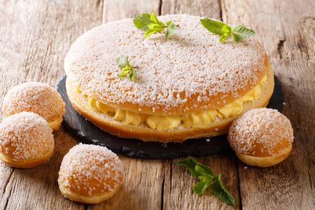 Delicate tropezienne tarte - brioche sandwich cake with cream close-up on the table. Horizontal Foto de archivo