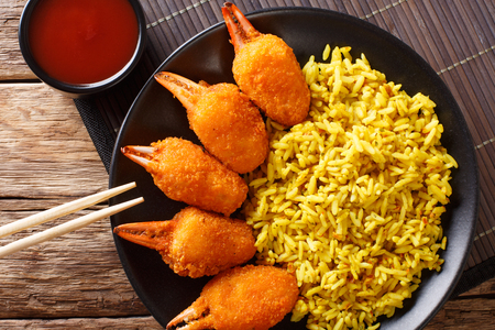 Deep fried crab claws in breadcrumbs of surimi with spicy yellow rice close-up on a plate on a table. Horizontal top view from above Stock Photo