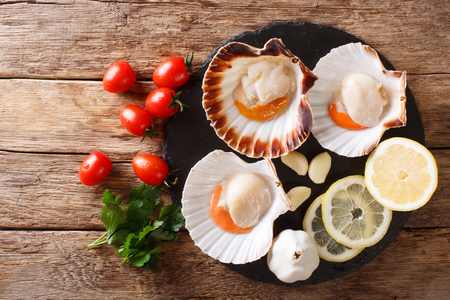 Delicious raw scallops in a shell and tomatoes, garlic, parsley and lemon close-up on a wooden table. Horizontal top view from above food background