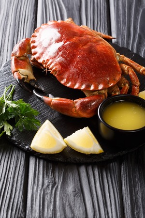 tasty boiled whole brown crab with sauce, lemon and parsley on a stone board close-up on a black table. vertical Stock Photo