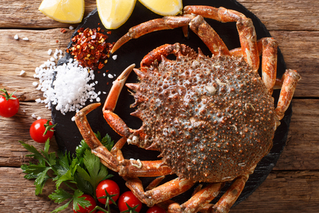 Preparation for cooking food spider crab with fresh ingredients close-up on a wooden table. horizontal top view from above Reklamní fotografie