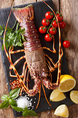 Preparation for cooking food spiny lobster or sea crayfish with fresh ingredients close-up on a wooden table. Vertical top view from above