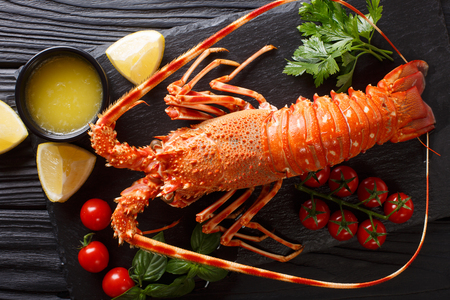 Delicious food: boiled spiny or rocky lobster with tomato, lemon and melted butter close-up on a black board. horizontal top view from above Stock Photo