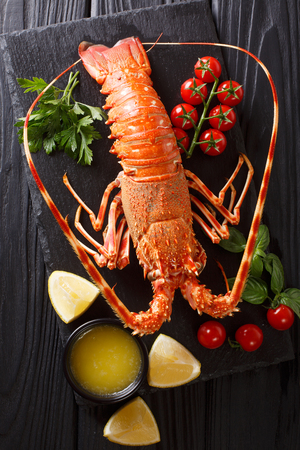 Luxurious boiled spiny lobster surrounded by fresh tomatoes, lemon, herbs and melted butter close-up on a black stone. Vertical top view from above
