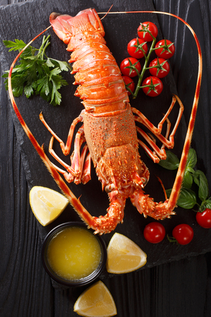 Delicious food: boiled spiny or rocky lobster with tomato, lemon and melted butter close-up on a black board. Vertical top view from above
