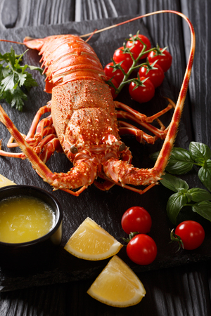 Expensive food: spiny boiled lobster with fresh tomato, lemon and melted butter close-up on black stone. vertical