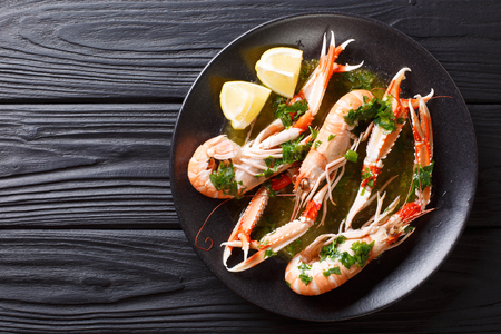 Gourmet seafood scampi or langoustine or Norway lobster are served on a black plate with sauce and lemon close-up. Horizontal top view from above Stock Photo