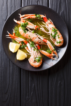 Gourmet seafood scampi or langoustine or Norway lobster are served on a black plate with sauce and lemon close-up. Vertical top view from above Stock Photo