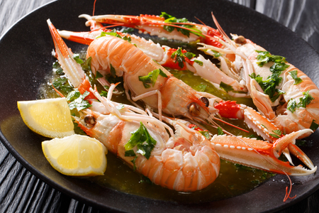 Restaurant meal. langoustine, scampi, Nephrops norvegicus with lemon and melted butter with parsley close-up on a plate on a black table. horizontal