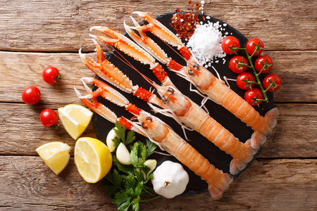 Luxury fresh raw langoustine, scampi with ingredients close-up on a wooden table. horizontal top view from above
