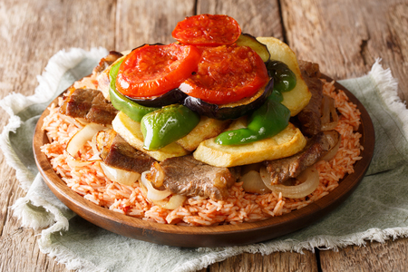 Home Arabic cuisine: Maklouba or Makloubeh or Makloubi rice with beef and vegetables close-up on a plate on a table. horizontal