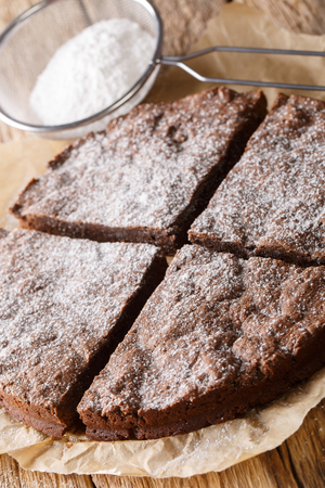Traditional Swedish kladdkaka chocolate cake sliced on parchment close-up on a table. vertical