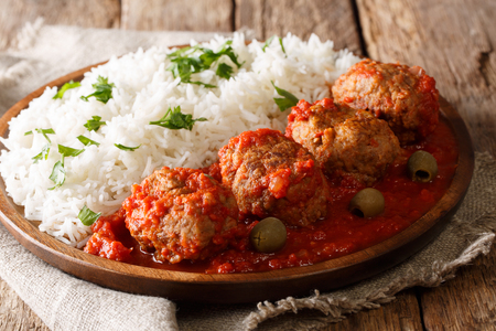 Traditional Greek meatballs in tomato sauce with rice close-up on a plate on a table. horizontal 版權商用圖片