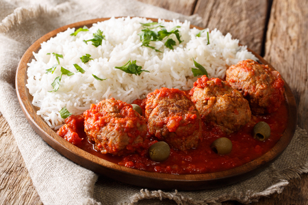 Greek food: Soutzoukakia baked meat balls in spicy tomato sauce served with rice close-up on a plate on the table. horizontal