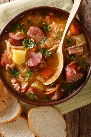 Czech traditional soup zelnacka of sauerkraut with sausages close-up in a bowl on the table. vertical top view from above Stock Photo