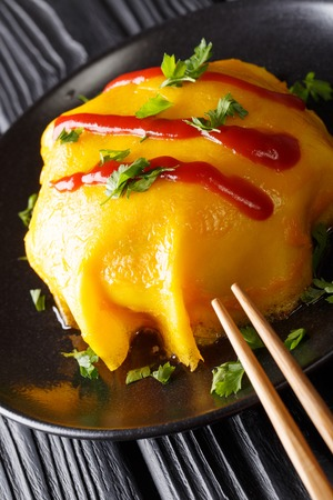 Japanese omurice omelette stuffed with rice, chicken and vegetables close-up on a plate on a table. vertical