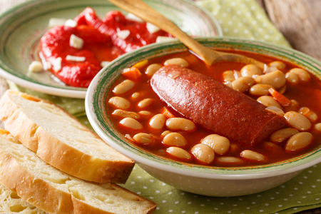 Pasulj (grah) bean soup with sausage is served with bread and bell pepper close-up on a plate on the table. horizontal