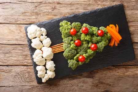 Beautiful food: Christmas tree of broccoli, cauliflower, tomatoes, pepper closeup on a table. Horizontal top view from above