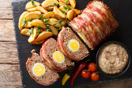Freshly cooked meat loaf with egg wrapped in bacon with potato wedges and vegetables close-up on a black background. Horizontal top view from above Standard-Bild - 109066524