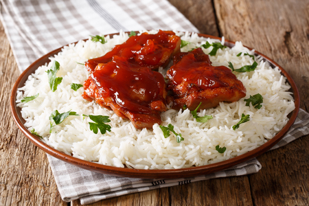 glazed Catalina chicken with spicy sauce and basmati rice close-up on a plate on the table. horizontal