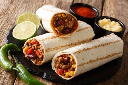 Mexican popular grilled burrito snack with beef and vegetables and with sauces close-up on the table. horizontal Zdjęcie Seryjne