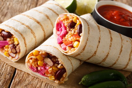 Fast food grilled veggie burrito with rice and vegetables close-up on the table. horizontal, rustic style Imagens