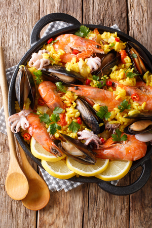 Spanish traditional cuisine: hot paella with seafood shrimps, mussels, fish, and baby octopuses close-up in a frying pan on the table. Vertical top view from above