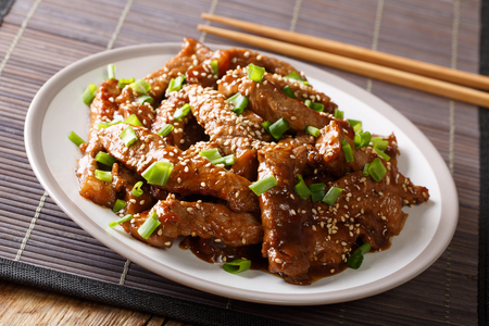 Asian stir-fried beef in teriyaki sauce with sesame and green onions closeup on a plate on the table. horizontal