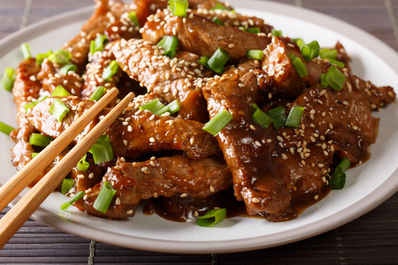 Asian food: Teriyaki beef with green onions and sesame close-up on a plate on the table. horizontal Stockfoto