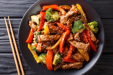 Asian teriyaki beef with bell pepper, broccoli and sesame close-up on a plate on the table. horizontal top view from above