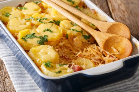 Bavarian baked food from sauerkraut with potatoes, bacon and cheese closeup in baking on the table. horizontal Reklamní fotografie