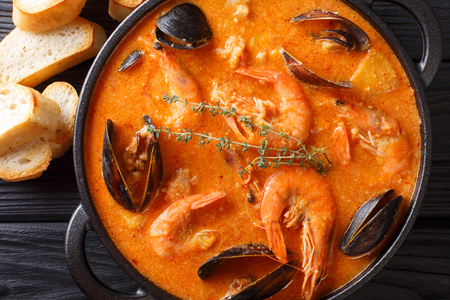 Spanish Suquet de Peix soup with seafood, potatoes, herbs and fish close-up in a pan on the table. Horizontal top view from above Stok Fotoğraf